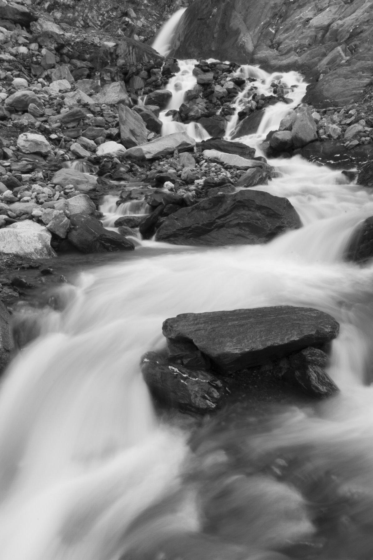 Glacial melt flowing over rocks.