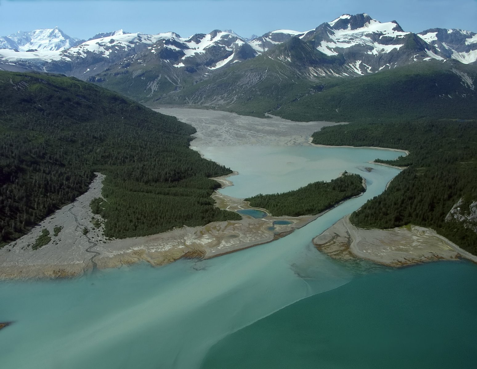 In 1928 the U.S. Navy flew a survey plane throughout Southeast Alaska taking aerial photos.  Those photos show that most of the bay shown in the middle of this image didn't exist back then – it was beneath the ice terminus of the Hugh Miller Glacier, which has now retreated back around the corner to the left.