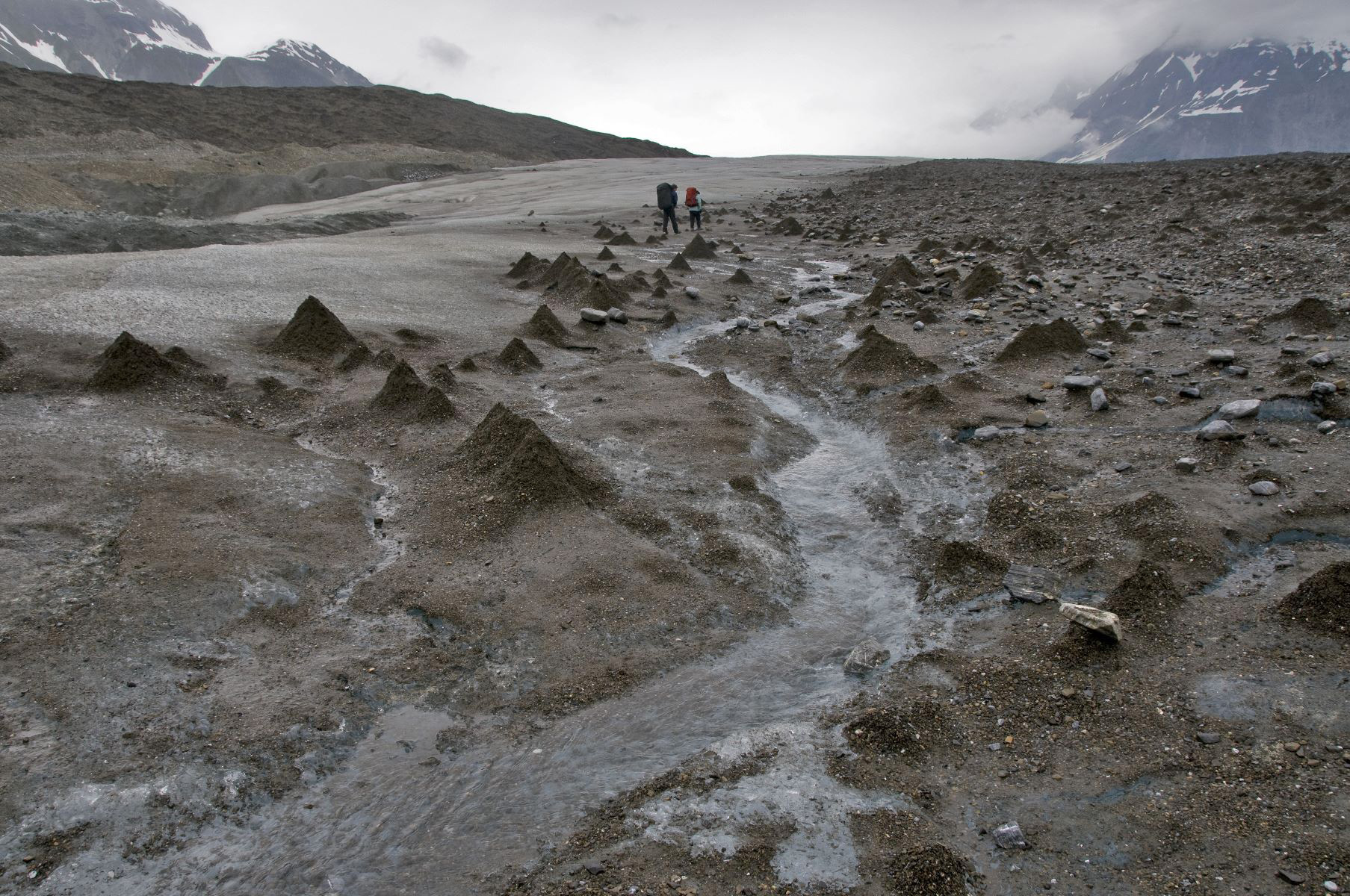 The cone shaped mounds are called glacier cones or debris cones.  They are mostly ice with a thin veneer of gravel and sand over a cone of ice.