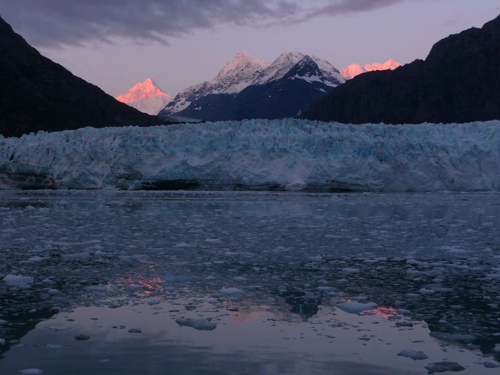 Soft sunset hues light the mountains behind the glacier.