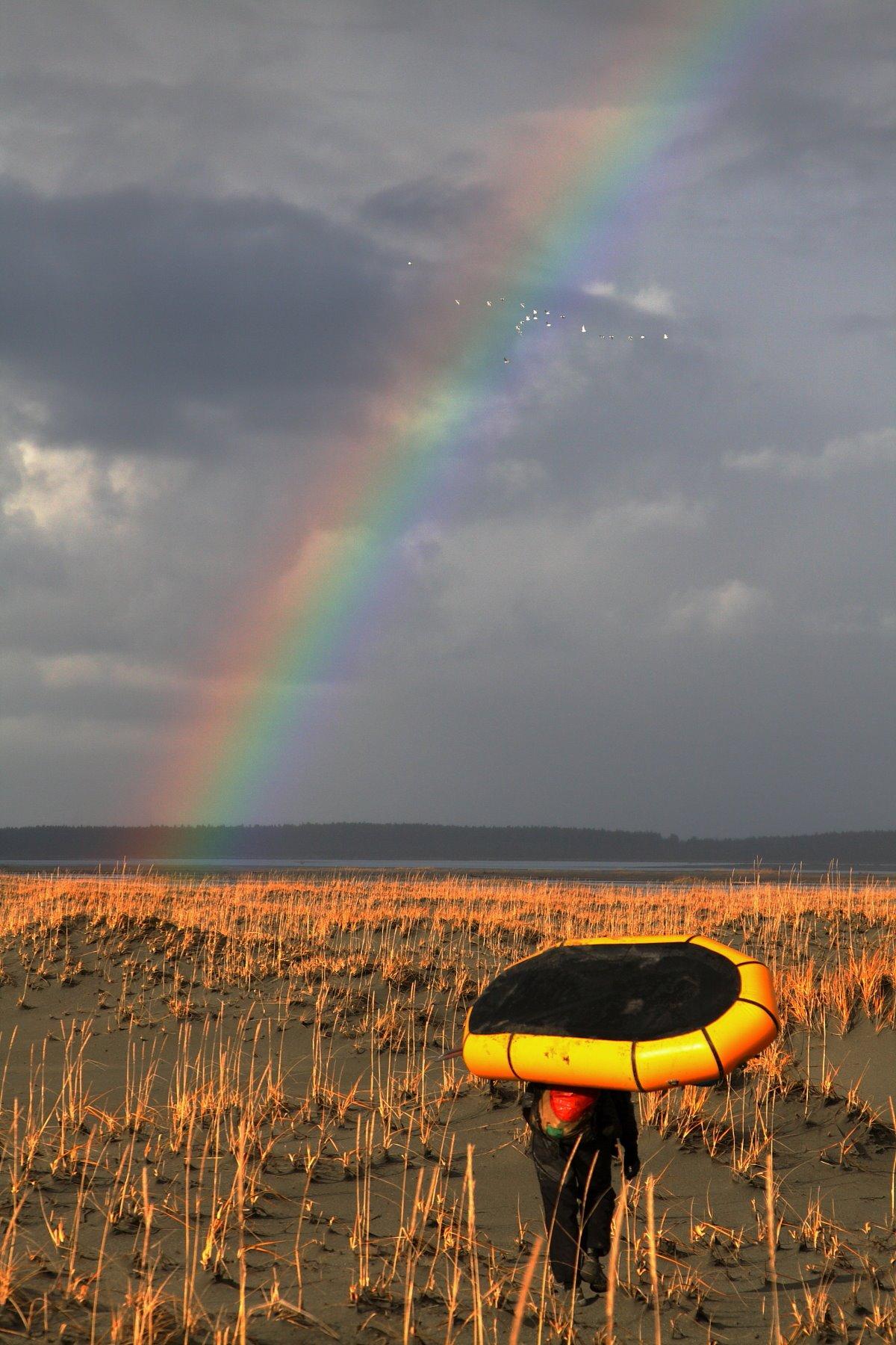 A rainbow glows against the dark grey sky, towards the crossing of Alsek River at Dry Bay