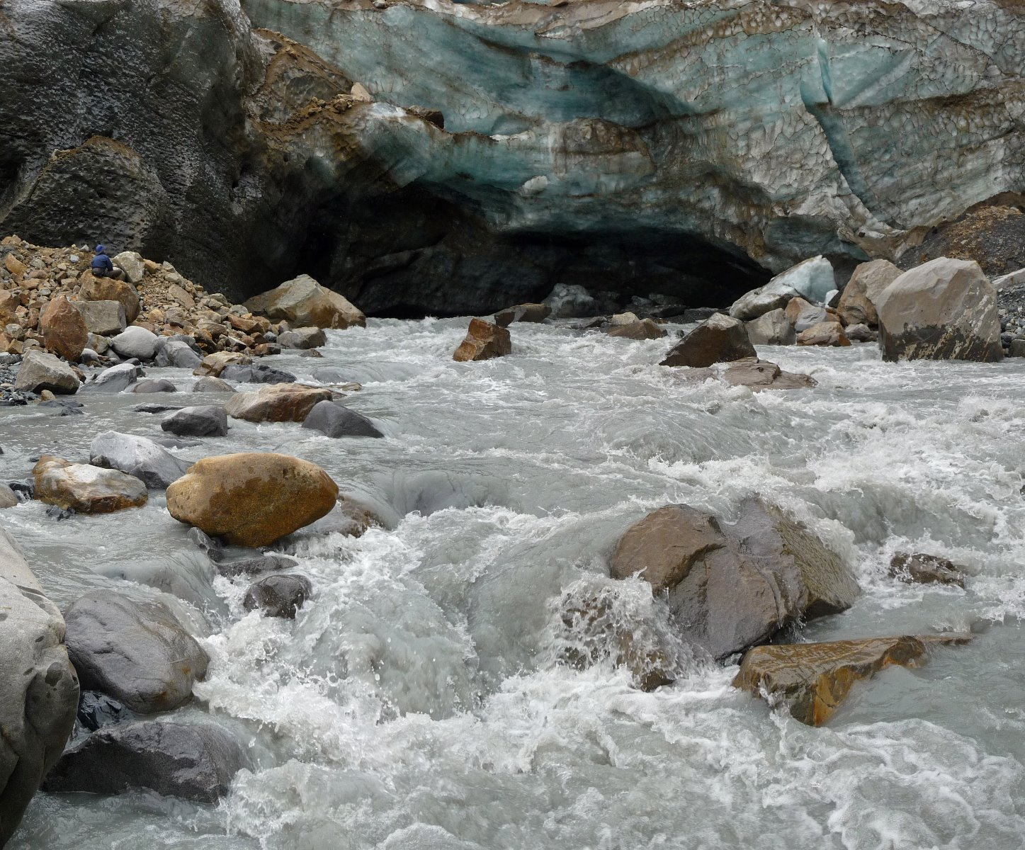 A turbulent river emerges from beneath a glacier.